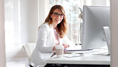 woman with glasses working at her desk