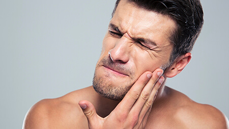 Lake Forest man having severe toothache with hand on jaw
