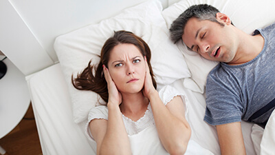wife covering ears while husband snores