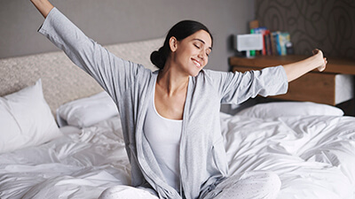 woman stretching arms after waking up
