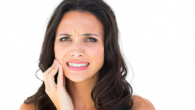 woman having toothache with hand on jaw