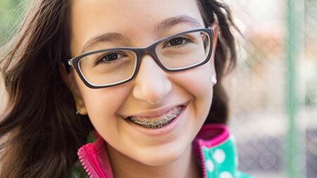 little girl with braces and glasses