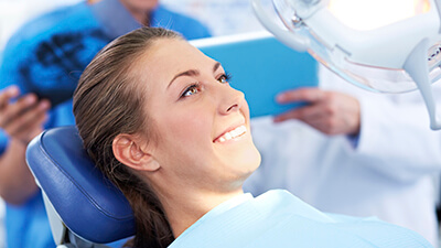 woman on exam chair under dental light